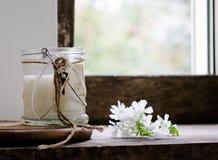 Aún vida rústica leche en un tarro de cristal, flores vintage, fondo de madera, ventana y recién hecho Imagen de archivo libre de regalías