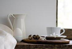 Aún vida rústica leche fresca, taza de té verde, y huevos contra un fondo rústico Fotos de archivo libres de regalías