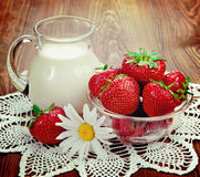 Aún vida rústica Leche y fresas en una tabla con las flores Fotos de archivo