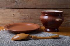Aún vida rústica Pote, cuchara y placa de arcilla en la servilleta de lino wo Imagen de archivo libre de regalías