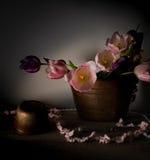 Aún vida rústica ramo de tulipanes en un lavabo de cobre en la tabla de madera Fondo negro Imagenes de archivo
