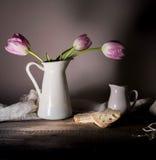 Aún vida rústica ramo de tulipanes, pan fresco, leche en una tabla de madera Fondo negro Imagenes de archivo