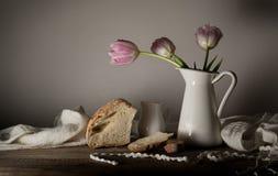 Aún vida rústica ramo de tulipanes, pan fresco, leche en una tabla de madera Fondo negro Imagen de archivo