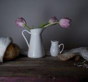 Aún vida rústica ramo de tulipanes, pan fresco, leche en una tabla de madera Fondo negro Fotos de archivo libres de regalías