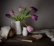 Aún vida rústica ramo de tulipanes, pan fresco, leche en una tabla de madera Fondo negro Fotografía de archivo libre de regalías
