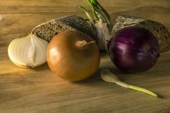 Aún vida rústica simple con las cebollas y el pan Imagenes de archivo