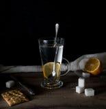 Aún vida rústica Té con el limón en un círculo grande en la tabla de madera Fondo negro Imagenes de archivo