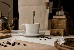Aún vida rústica taza de café, de amoladora de madera hecha a mano, de caldera de oro y de granos de café en la tabla vendimia Imagenes de archivo