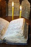 Aún vida religiosa con el libro viejo abierto y las velas ardientes Foto de archivo