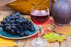 Aún vida retra con el vino rojo, el libro, el reloj y la uva Imagen de archivo