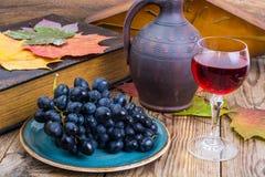 Aún vida retra con el vino rojo, el libro, el reloj y la uva Imagenes de archivo