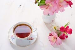 Aún vida retra con la taza de té y de flores Foto de archivo