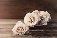 Aún vida retra con las flores color de rosa del vintage y el libro antiguo Composición nostálgica en la tabla de madera vieja Imagen de archivo
