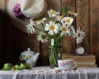 Aún vida retra con las flores del jardín, los libros y una taza Fotos de archivo