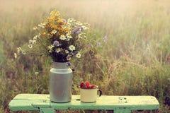 Aún vida retra con las flores y las bayas en el landscap rústico Imágenes de archivo libres de regalías