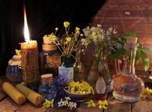 Aún vida retra con las velas y las flores en las botellas de cristal contra fondo de madera Imagen de archivo