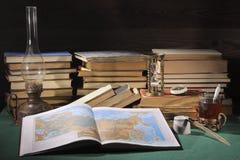 Aún vida retra En la mesa, hay: una lámpara de keroseno, un reloj de arena, un portapluma, una tinta-botella vieja y libros viejo Imagen de archivo