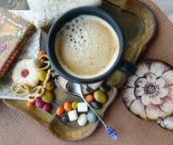 Aún vida retra Una taza de café con crema, las galletas y el caramelo en una bandeja Imagen de archivo