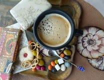 Aún vida retra Una taza de café con crema, las galletas y el caramelo en una bandeja Fotos de archivo libres de regalías