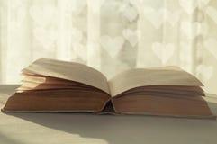 Aún vida romántica del libro viejo abierto bajo luz del sol caliente Fotos de archivo libres de regalías