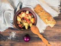 Aún vida rural Carne cocida con las patatas, el pan, la sal y la cebolla en el fondo de la tabla de madera y del paño grueso Imagen de archivo libre de regalías