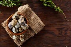 Aún vida rural con el cuenco lleno de huevos codornices, huevos en una servilleta casera, boj en el fondo de madera, visión super Imagen de archivo