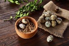 Aún vida rural con el cuenco lleno de huevos codornices, huevos en una servilleta casera, boj en el fondo de madera, visión super Foto de archivo libre de regalías