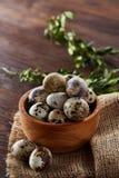 Aún vida rural con el cuenco lleno de huevos codornices, huevos en una servilleta casera, boj en el fondo de madera, visión super Imagen de archivo libre de regalías