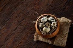 Aún vida rural con el cuenco lleno de huevos codornices, huevos en una servilleta casera, boj en el fondo de madera, visión super Imagenes de archivo