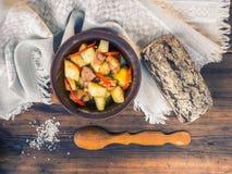 Aún vida rural con las patatas cocidas con la carne, las verduras, el pan y la sal en el fondo de la tabla de madera y grueso Fotos de archivo libres de regalías