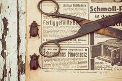 Aún vida rural con las tijeras oxidadas y los insectos que corren en el fondo con el periódico viejo Imagen de archivo