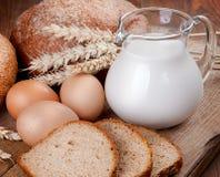 Aún vida rural Pan, leche y huevos en el tablero Fotos de archivo