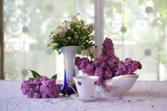 Aún-vida sobre una lila y una taza de té Foto de archivo
