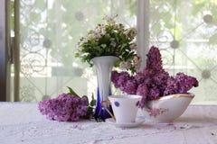 Aún-vida sobre una lila y una taza de té Foto de archivo libre de regalías