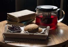 Aún-vida, tabla de madera cubierta, desayuno con té, pasas y galletas de la nuez imagen de archivo libre de regalías