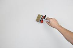 A供以人员有一支画笔的胳膊在灰色墙壁上 库存图片