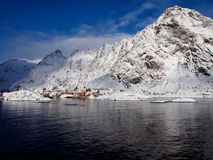 A小渔夫` s村庄在Lofoten,在积雪覆盖的峰顶下的挪威的 库存照片