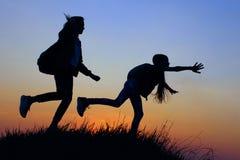 A少女剪影在山上面的 有背包的少女享受日落的 使用女性的朋友户外 免版税库存照片