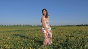 A微笑的妇女画象站立在礼服的A开花的黄色领域的 影视素材