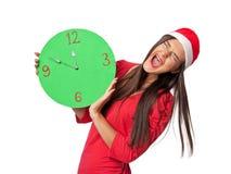 a的美丽的女孩在圣诞老人的生气和拿着绿色时钟的帮手帽子 免版税库存照片