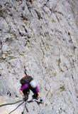上升在一张岩石面孔的登山家妇女 免版税图库摄影