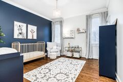 Free A Baby`s Room With A Gold Crib And Blue Accent Wall. Royalty Free Stock Image - 191117596