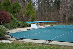 Free A Backyard Swimming Pool With Diving Board And Pool Slide Tarped Up And Closed Down For Winter Royalty Free Stock Photography - 166439987