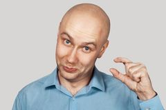 Free A Bald Guy Shows A Hand Gesture Meaning A Very Small Amount Of Something Stock Photos - 168051783