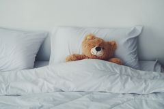 A Bear Doll Laying On White Bed. Royalty Free Stock Photos
