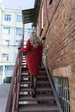 A Beautiful Blonde Girl Wearing A Red Coat And Gloves Climbs A Rusty Metal Ladder Near A Brick Wall. Fashion, Commercial, Royalty Free Stock Photography