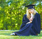 A Beautiful Graduate Sitting On The Lawn Royalty Free Stock Photos