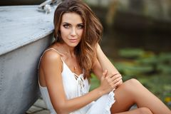Free A Beautiful Tanned Girl In A White Dress Sits By The Boat And Is Stock Photos - 110879413
