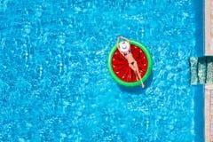 Free A Beautiful Woman In Bikini Takes A Sunbath On A Watermelon Shaped Float Over Blue Pool Water Stock Image - 184435091