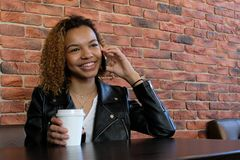 A Beautiful Young African-American Woman In A Jacket With A White Paper Glass In One Hand, Sitting At A Table And Smiling While Ta Royalty Free Stock Photos